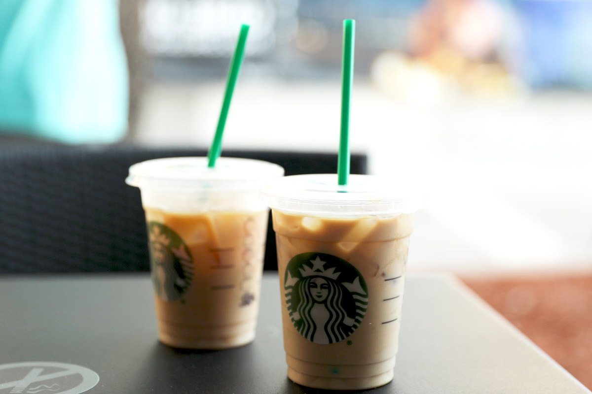 Iced coffees from Starbucks sit on a table outside.